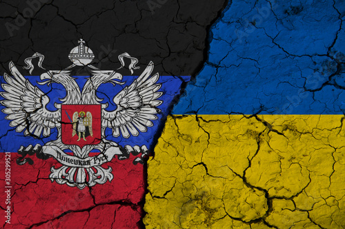 Photo Flag of Ukraine and Donetsk People's Republic on textured cracked earth