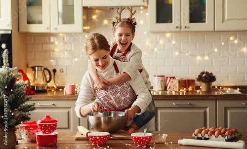 Obraz happy family mother and child bake christmas cookies. - fototapety do salonu
