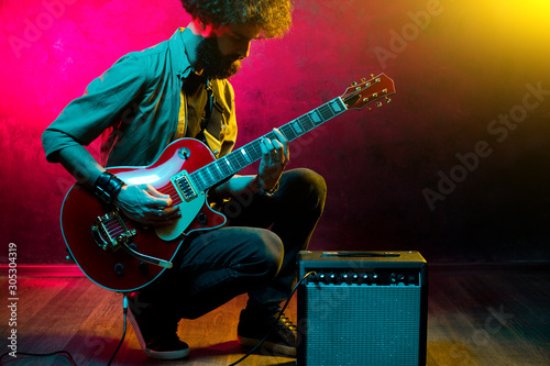 Portrait of hipster man with curly hair with red guitar in neon lights. Rock musician is playing electrical guitar. - 305304319