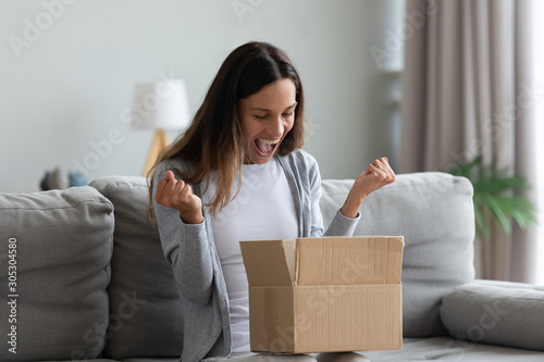 Fotografie, Obraz Woman screaming with joy opens carton parcel box feels happy