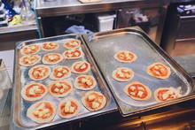 Tomato And Mozzarella Mini Pizzas On Board.