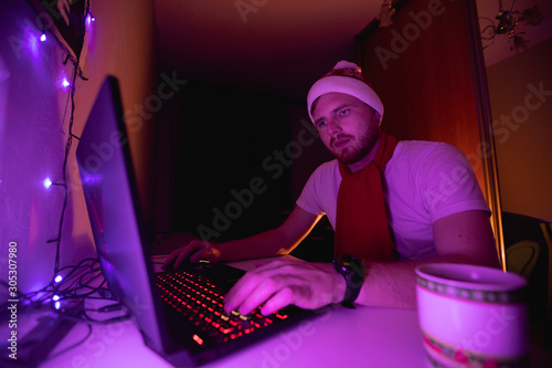 Платно Christmas freelancer working in laptop at the home