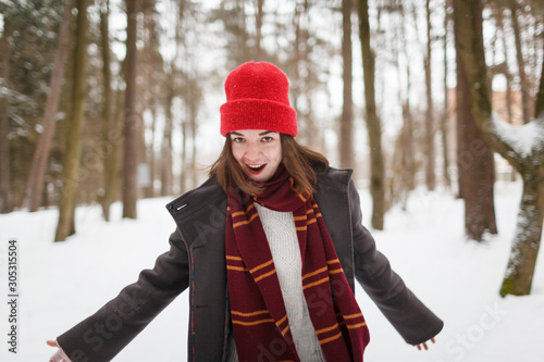 Cuadros en Lienzo Young woman with brown hair and gryffindor scarf is dancing in winter forest