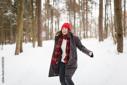 Fotomural Young woman with brown hair and gryffindor scarf is dancing in winter forest