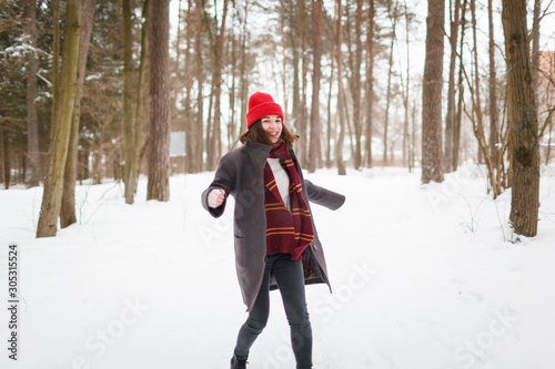 Obraz na plátně Young woman with brown hair and gryffindor scarf is dancing in winter forest