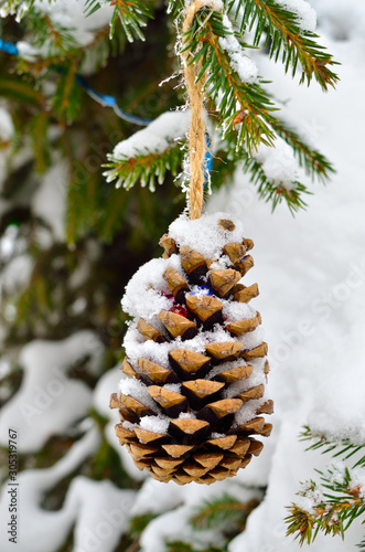 Snow covered branches of the Christmas tree decorated with toys Slika na platnu