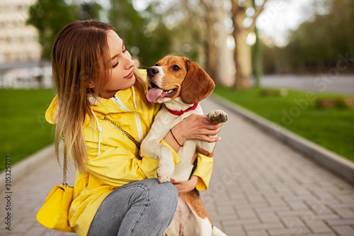 Leinwand Poster Woman hugging adorable dog while walking in street