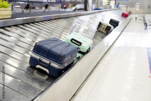Fototapeta Suitcase on luggage conveyor belt at airport