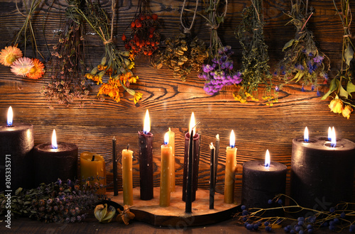 Foto  Still life with burning candles and dry herbs on witch table.