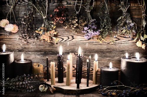 Tablou Canvas Black candles, herbs and flowers against wooden wall on witch table