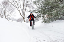 Teenage Boy Riding A Fat Tire Bicycle In Winter Snow