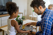 father and Daughter play chess game in house