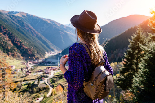 Stylish trendy hipster woman traveler in a felt hat with brown backpack stands o Fototapet