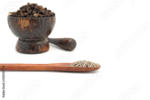 closeup the black pepper in Wooden mortar on white background , selective focus. Herbal Medicines.