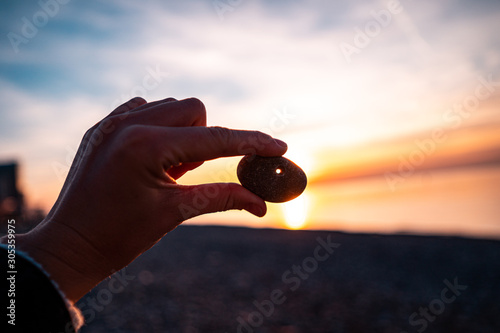 Photo Person holds a stone with a hole at sunset