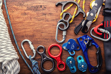 Climbing Equipment Outdoor For A Mountain Trip Or Rescue.With Rope Carabiners Ascender Belay/rappel Device, Over Concrete Background With Copy Space On Wooden Background, Top View. Travel Concept