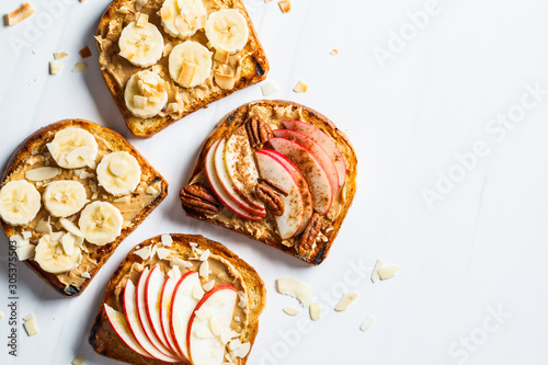 Leinwand Poster Peanut butter toasts with banana and apple on a gray background, flat lay