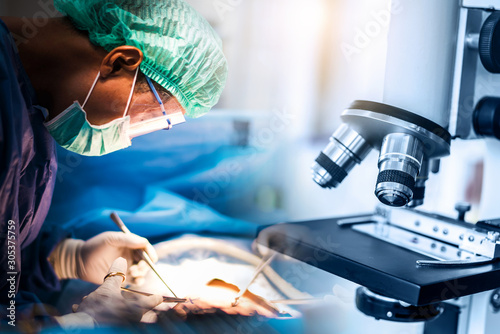 Fotografía  Scientist or doctor working in the operating room with microscope and glassware,