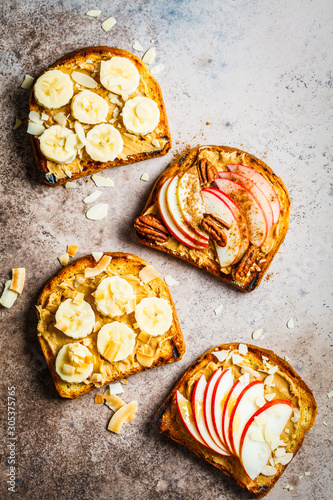 Cuadros en Lienzo Peanut butter toasts with banana and apple on a gray background, flat lay