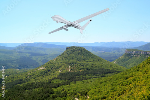 Spy unmanned aerial vehicle (UAV) flies over mountain landscape, rocks and valle Canvas Print
