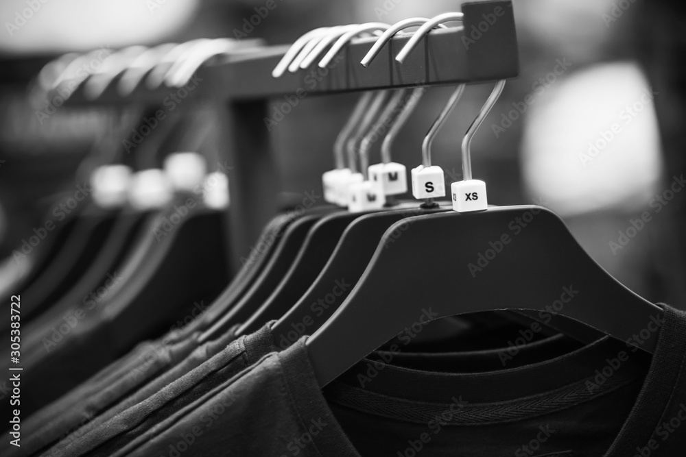 Fototapeta A black-and-white image of hangers hanging in the store, on which hang simple casual t-shirts of different sizes.