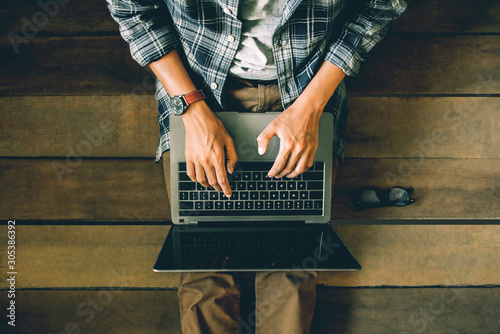 businessman sitting on wooden floor with coffee cup and glasses using laptop working at home to send and send reply to email Message customer service