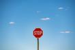 Stopschild vor blauem Himmel mit kleinen Wolken