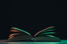 Beautiful Open Old Book In The Color Light On A Table And Night Background.