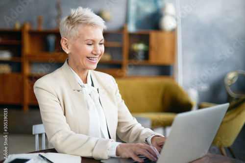 Obraz Picture of stylish cheerful middle aged female in elegant suit enjoying online communication while working in office, sitting at desk in front of open portable computer, keyboarding and smiling - fototapety do salonu