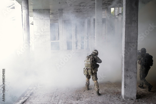 Photo Two military soldiers storming a destroyed building with terrorists in a smoke f