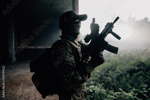 Army soldier in camouflage standing with assault rifle in hand among the stone jungle showing class Wallpaper Mural
