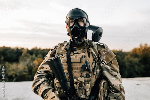 Fotografía  Portrait of a military soldier in a smoke curtain with an assault rifle in a gas