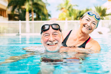 Couple Of Two Seniors Hugged In The Water Of Swimming Pool - Active Man And Woman Doing Exercise Together At The Pool - Hugged With Love