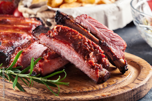 Fototapeta Spicy barbecued pork ribs served with BBQ sauce obraz