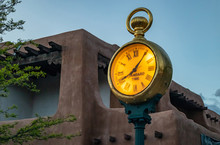 Gold Post Clock Outdoor In Santa Fe Plaza, Traditional Rchitecture And Blue Sky At Sunset Background, New Mexico, US.