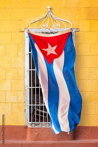 Cuban flag hanging at the window of a colorful house in a street of Trinidad, Cu Wallpaper Mural
