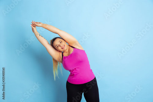 Young caucasian plus size female model's training on blue background Wallpaper Mural