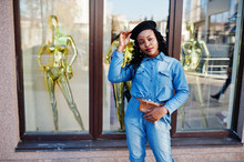 Stylish Fashionable African American Women In Jeans Wear And Black Beret Against Modern Building With Three Golden Mannequins.