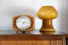 Mid Century Decor.  Vintage Or Retro Clock In Shape Focus On A Sideboard With A Background Retro Blown Glass Mushroom Lamp