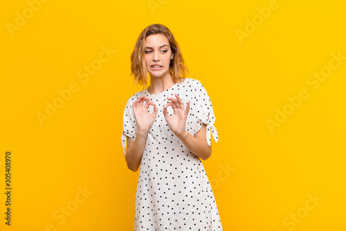 Photo young blonde woman feeling disgusted and nauseous, backing away from something n