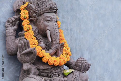 Ganesha sitting in meditating yoga pose in front of hindu temple Canvas Print