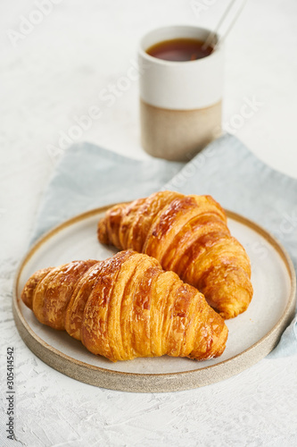 Two delicious croissants on plate and hot drink in mug Wallpaper Mural