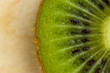 Closeup of a kiwi on the wooden background. Cut piece of kiwi fruit with skin on a wooden table
