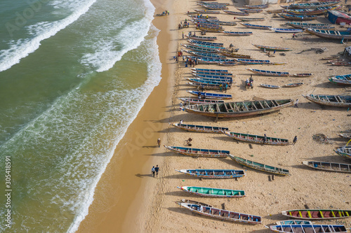 Foto auf Leinwand Khaki Aerial view of fishing village, pirogues fishing boats in Kayar, Senegal. Photo made by drone from above. Africa Landscapes.