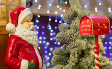 A Big Santa Claus Figure Is Standing Next To A Wooden Door In Front Of A Christmas Tree. Next To It Is A Red Mailbox With The Santa Claus Lettering. In The Background Are Many Lights With Bokeh.