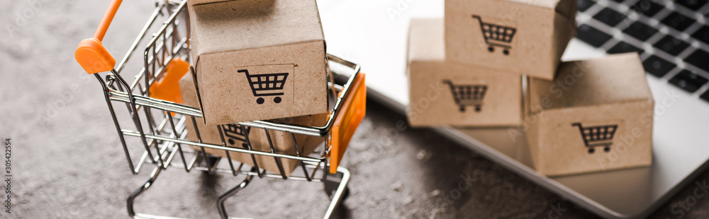 Fototapeta panoramic shot of toy shopping cart with small carton boxes near laptop, e-commerce concept