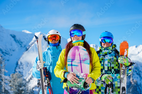 Fotomural  Two men and woman with snowboard and skis standing on snow resort against backdrop of mountain