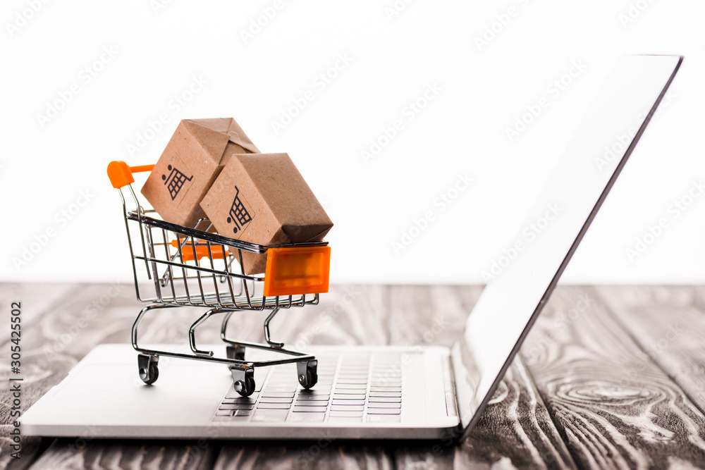 Fototapeta selective focus of toy shopping cart with small carton boxes on laptop isolated on white, e-commerce concept