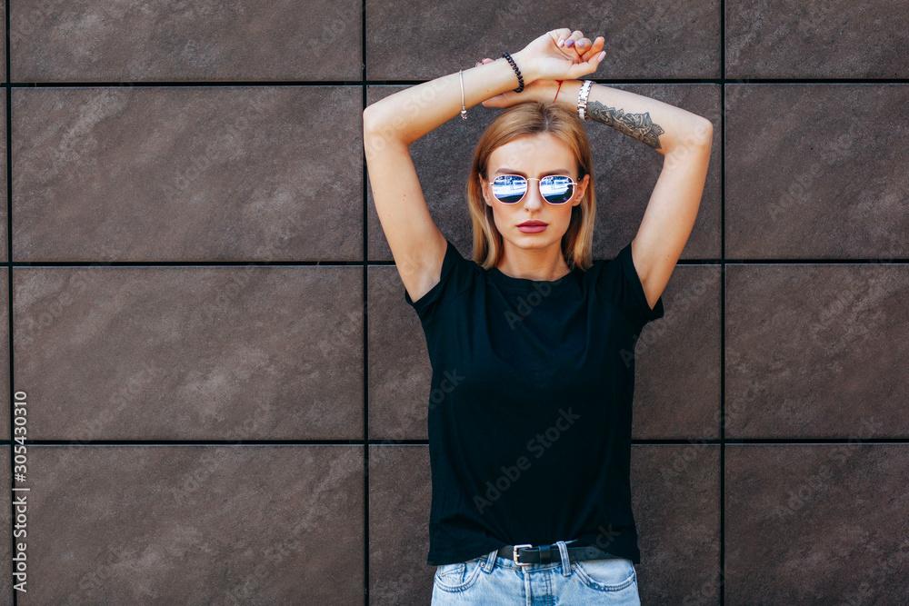 Fototapeta Girl wearing black t-shirt, glasses and leather jacket posing against street , urban clothing style. Street photography