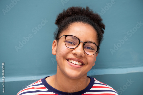 Fototapeta Close up of smiling young mixed race girl with glasses against blue wall obraz